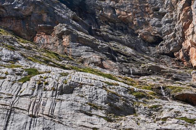 Hoge steile rotswand met een kleine waterval die eraf stroomt