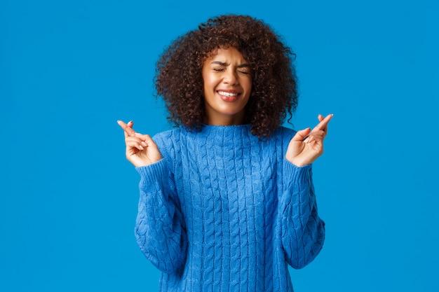 Hoge verwachtingen concept. opgewonden en bezorgd afro-amerikaanse jonge schattige vrouw in de winter trui gekruiste vingers veel geluk, ogen sluiten en tanden op elkaar klemmen als droom uitkomen, wens doen