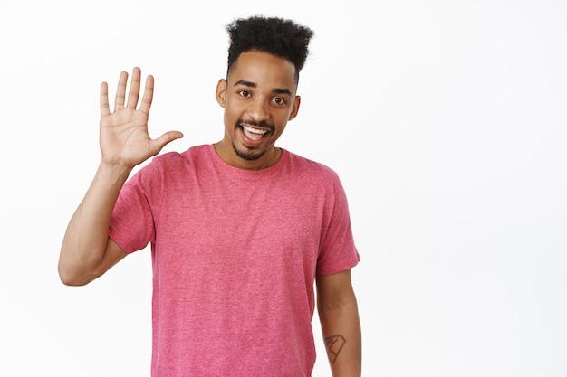 Hoge vijf. glimlachende afro-amerikaanse man die hand opsteekt, hallo zwaait met vriendelijke gezichtsuitdrukking, groet, hallo gebaar maakt, in roze t-shirt op wit staat