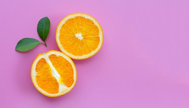 Hoge vitamine c, sappig en zoet. vers oranje fruit met groene bladeren op roze.