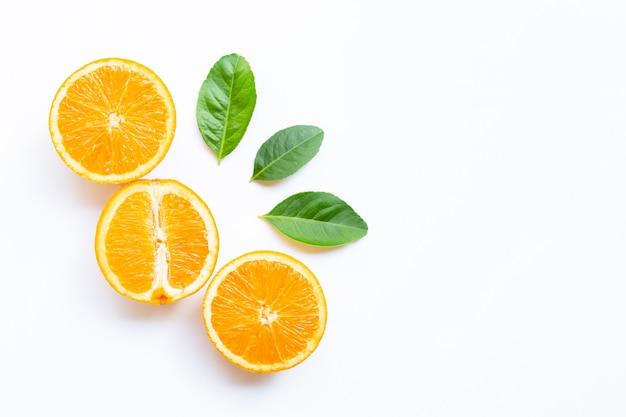 Hoge vitamine c, sappig en zoet. vers oranje fruit met groene bladeren op wit.