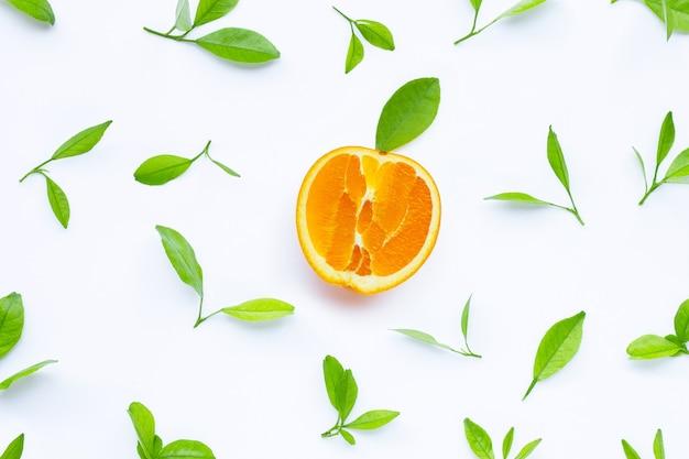 Hoge vitamine c, sappig en zoet. vers oranje fruit met groene bladeren op witte achtergrond.