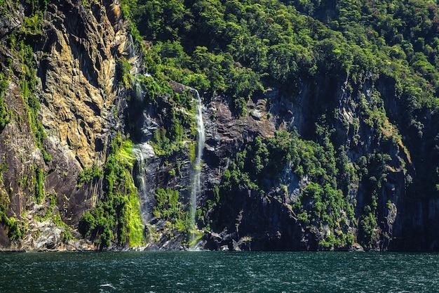 Hoge waterval in milford sound, nieuw-zeeland, foto genomen vanaf cruise ferry