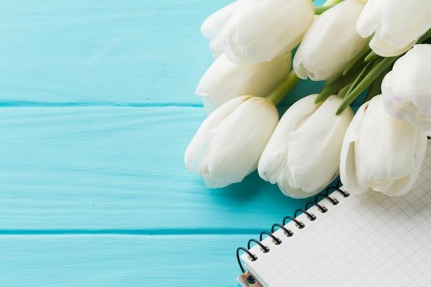 Hoge weergave boeket van tulpenbloemen en notitieblok