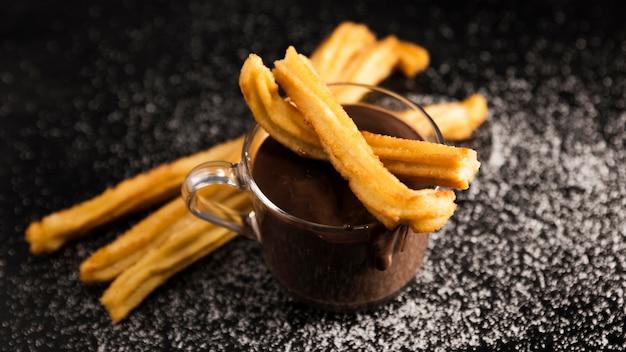 Hoge weergave churros en kopje gesmolten chocolade