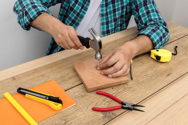 Hoge weergave handen met hamer en spijkers