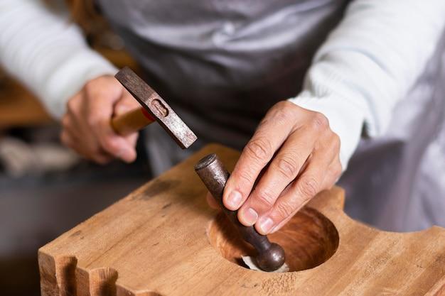 Hoge weergave klusjesman hameren op een stuk metaal