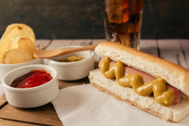 Hoge weergave van een hotdog met mosterd op een houten bord met potten met ketchup en mosterd, op de achtergrond een portie chips en een frisdrank. fastfood-concept.