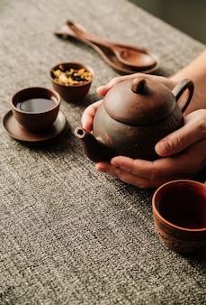 Hoge weergave van theepot wordt gehouden door de mens