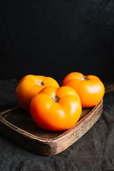 Hoge weergave van volwassen oranje tomaten op snijplank