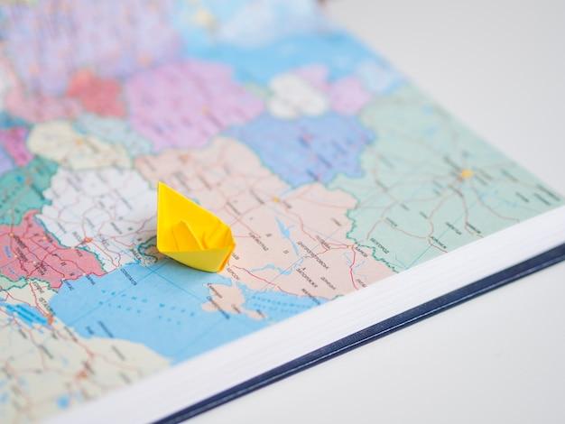 Hoge weergave van wereldkaart en papier boot