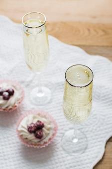 Hoge weergave witte wijnglazen en cupcakes