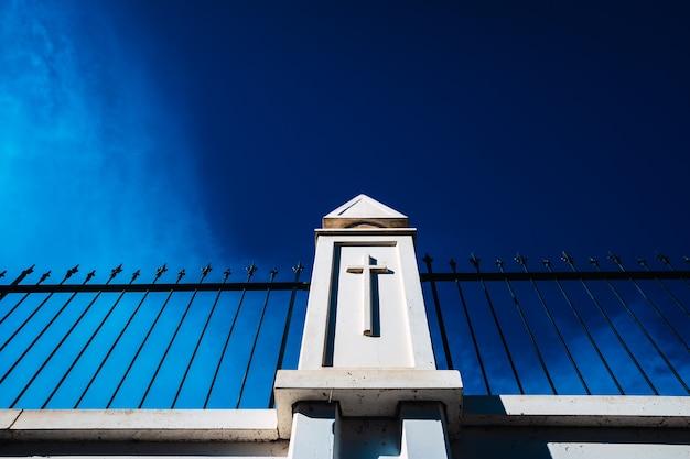 Hoge witte betonnen muren met metalen staven scheiden de doden van een buitenbegraafplaats