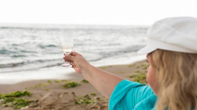 Hoger de holdingsglas van de toeristenvrouw bij het strand