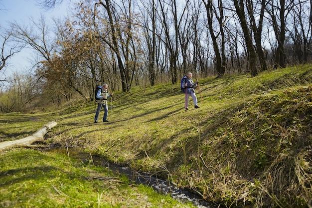 Hoger en sterker worden. leeftijd familie paar man en vrouw in toeristische outfit wandelen op groen gazon in zonnige dag in de buurt van kreek