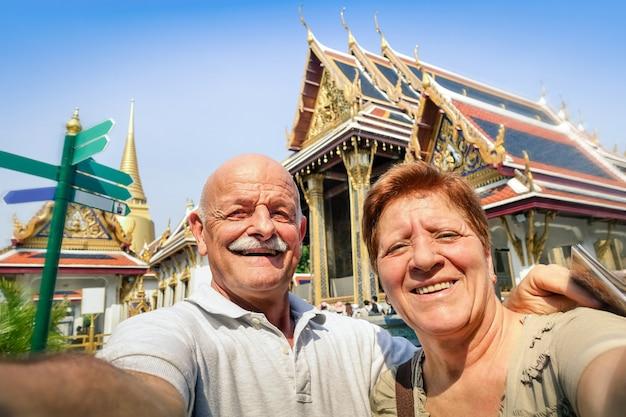 Hoger gelukkig paar die een selfie nemen bij grote paleistempels in bangkok