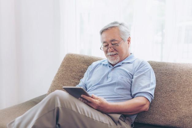 Hoger mannetje die een smartphone, het glimlachen gebruiken voelen thuis gelukkig op bank - bejaard concept