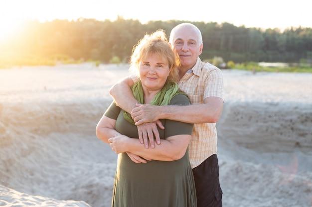 Hoger ouder kaukasisch paar samen in park in de zomer. vrouw en man knuffelen en lachen met geluk. mooie liefdesrelatie en verzorging van bejaarde ouderen.