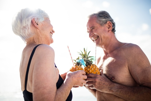 Hoger paar dat ananascocktail op strand heeft