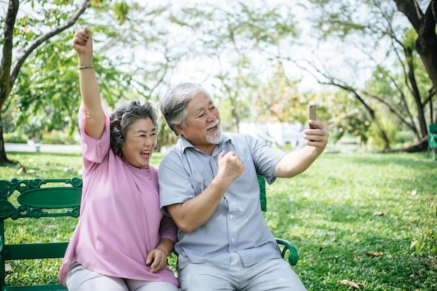 Hoger paar dat een selfiefoto met slimme telefoon in een park neemt