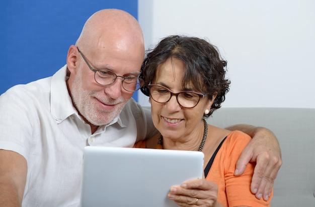 Hoger paar dat een tablet en het glimlachen gebruikt