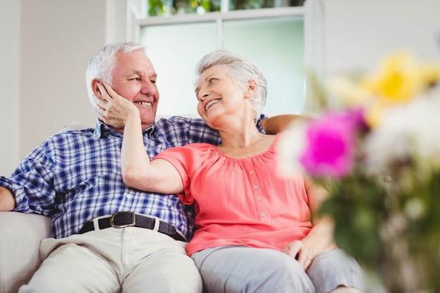 Hoger paar dat elkaar bekijkt en in woonkamer glimlacht