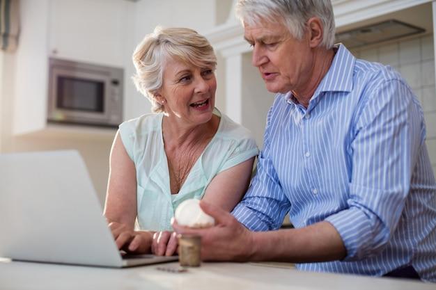 Hoger paar dat geneeskunde controleert op laptop in keuken