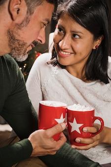 Hoger paar dat hete chocolade drinkt die bij elkaar staart