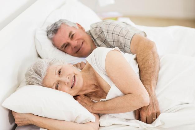 Hoger paar dat in bed bij de camera glimlacht
