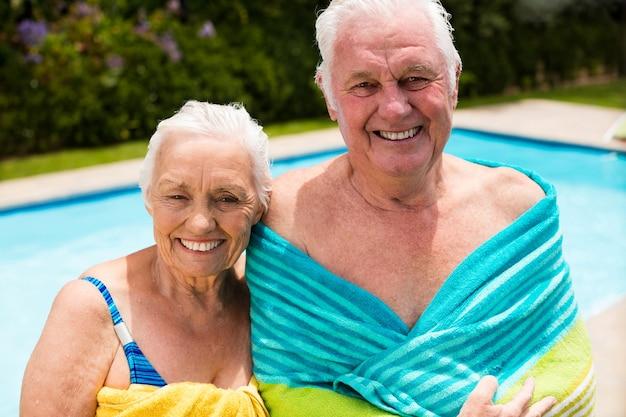 Hoger paar dat in handdoek bij poolside wordt verpakt