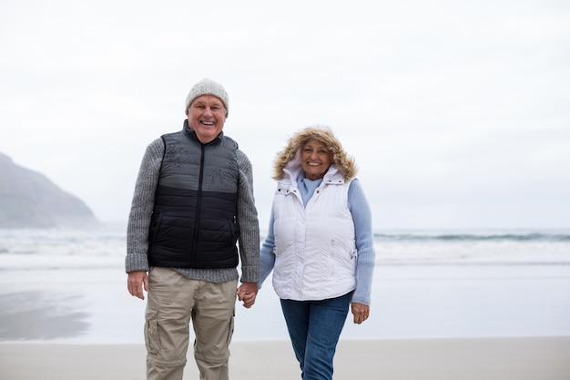 Hoger paar dat met holdingshanden op het strand loopt