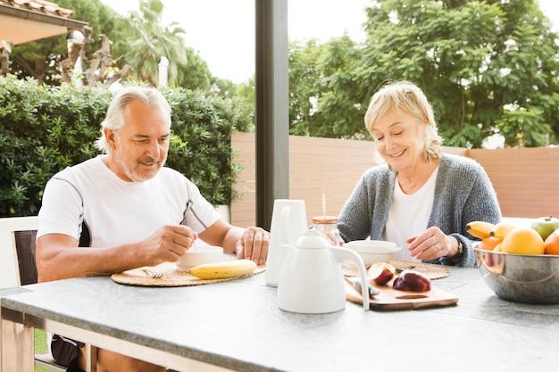 Hoger paar dat ontbijt in tuin heeft