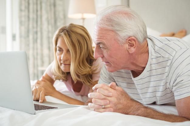 Hoger paar dat op bed ligt en laptop met behulp van