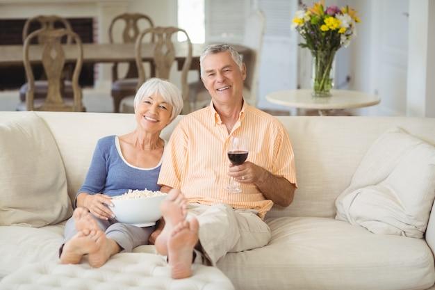 Hoger paar dat popcorn en glas wijn in woonkamer heeft