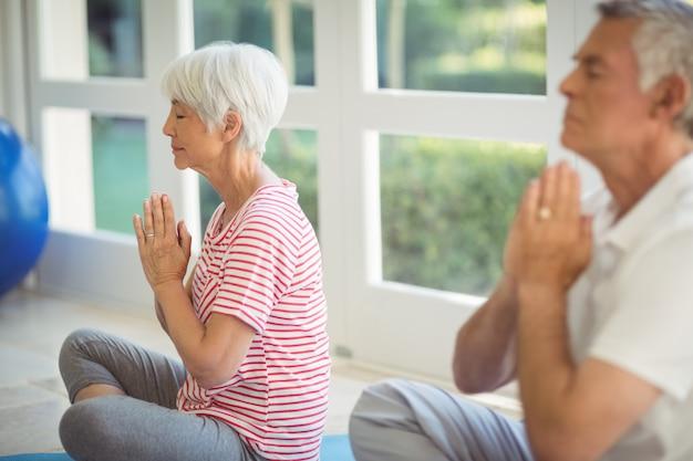 Hoger paar dat yoga op oefeningsmat uitvoert