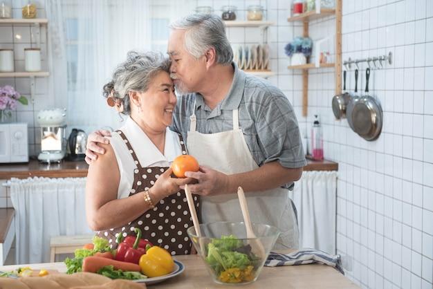 Hoger paar die pret in keuken met gezond voedsel hebben - gepensioneerden die maaltijd thuis koken met man en vrouw die lunch met biogroenten voorbereiden - gelukkig bejaard concept met rijpe grappige gepensioneerde.