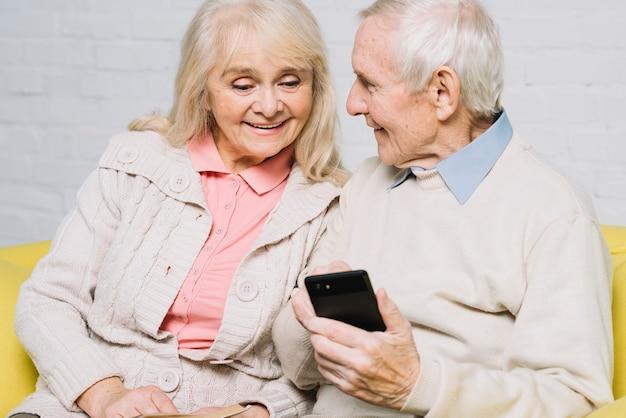 Hoger paar die smartphone gebruiken