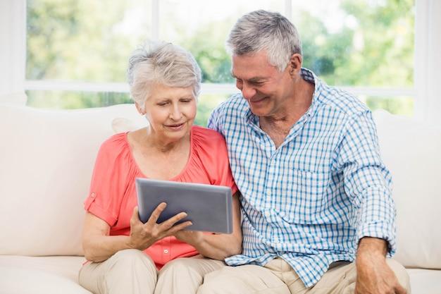 Hoger paar die tablet op de bank gebruiken