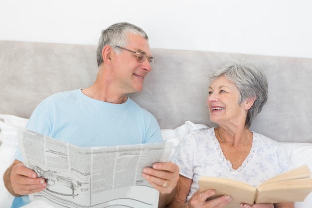 Hoger paar met krant en boek in bed