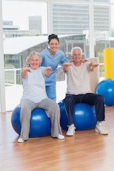 Hoger paar op exercisbal met trainer