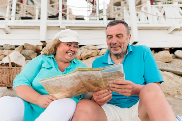 Hoger toeristenpaar dat kaart op het strand bekijkt