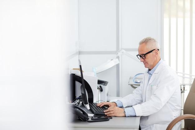 Hogere arts die computer met behulp van op het werk