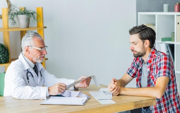 Hogere arts die met patiënt spreekt