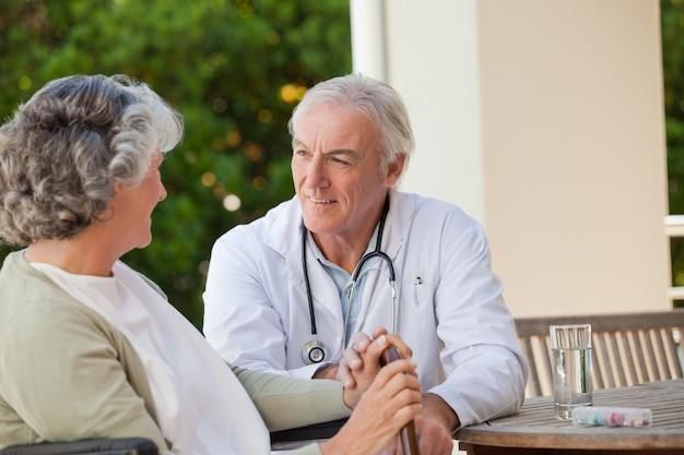 Hogere arts die met zijn rijpe patiënt spreekt