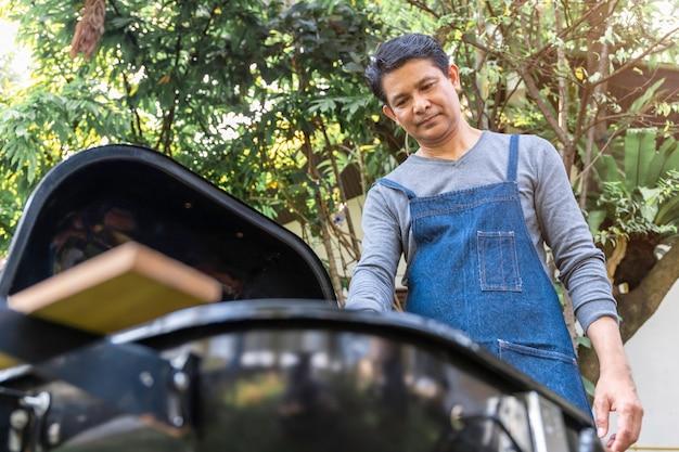 Hogere aziatische mens die schort draagt en een barbecuepartij in het park heeft.