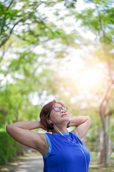 Hogere aziatische ontspannen vrouw luisterend aan muziek in het park