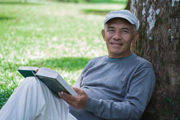 Hogere aziatische oude mens die een boek in openlucht leest