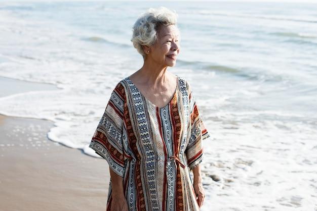 Hogere aziatische vrouw bij het strand