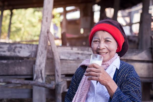 Hogere aziatische vrouw die een glas melk thuis in platteland van thailand houdt.