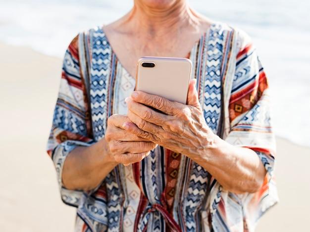 Hogere aziatische vrouw die een telefoon met behulp van bij het strand